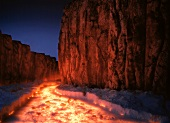 Glowing lava flow between steep rocks