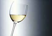 A glass of white wine held at an angle