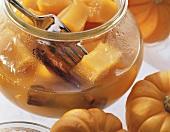 Orange pumpkin with cinnamon sticks in open jar with fork