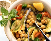 Chick pea stew with mint in deep plate with cutlery