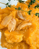 Pumpkin puree with cloves of garlic and sprig of thyme