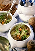 Bread soup with vegetables and bacon in small soup tureens