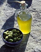 Olive oil & a bowl of green olives on stone background