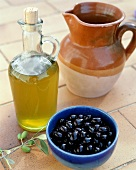 Olive oil, a bowl of black olives & an earthenware jug