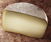 Cantal, a French hard cheese on brown background