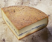 Morbier, a French semi-hard cheese, on light brown background