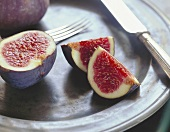 Figs, cut into, on a tin plate with cutlery