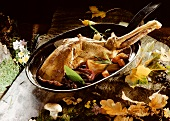 Leg of venison with vegetables in a pan; forest decoration