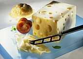 Emmental cheese with cheese knife, two tomato halves & roll