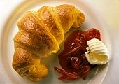 Croissant, jam and butter curl on a plate