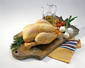 Whole chicken, vegetables, spices and oil on a chopping board