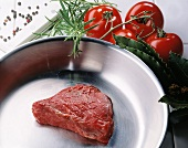 Fillet steak in a pan; tomatoes, herbs, spices