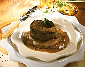 Beef fillet with truffles on slice of bread in pepper sauce