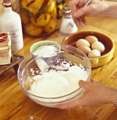 Whipping cream with whisk in a bowl