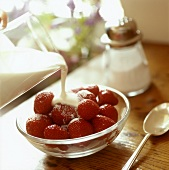Pouring creaming over strawberries in a bowl