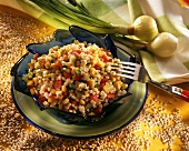 Pearl barley salad with vegetables on plate with fork