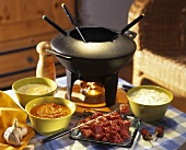 Meat fondue with three dips and fondue pot on a table