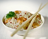 Rice noodles with shrimps in a bowl with chopsticks