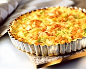 Quiche with celery and shrimps in the baking dish