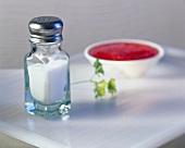 Salt in salt cellar, behind tomato sauce in a dish
