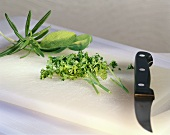 Various herbs, some chopped, on chopping board