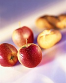 Three fresh apples and two bread rolls