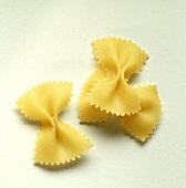 Three farfalle (pasta bows) on white background