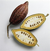 Cocoa beans, one halved, on a white background