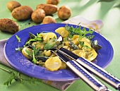 Potato and asparagus salad with rocket on blue plate