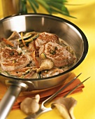 Slices of pork fillet & creamed mushroom & vegetables in pan