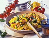 Vegetable paella with chicken breast in a clay dish
