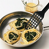 Making fried spaghetti nests with spinach