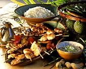 Poultry and shrimp kebabs with peanut sauce and rice