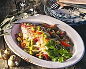 Gilthead bream with vegetables, baked in parchment, on platter