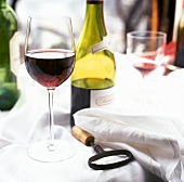 Glass of red wine on tablecloth, corkscrew, red wine bottle