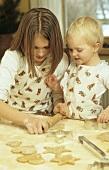Two children baking cinnamon stars