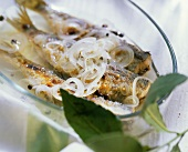 Pickled herrings with onions in glass dish
