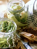 Spiced beans and mustard gherkins in jars; Peasant bread