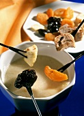 White chocolate fondue with dried fruit and raisin bread