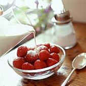 Pouring milk over strawberries in a small bowl