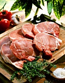 Pork chops on a chopping board; Herbs; Salt