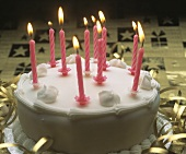 White birthday cake with ten pink candles