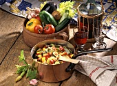 Ratatouille in a copper pan;  fresh vegetables; red wine