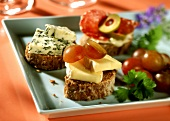 Walnut ring snacks, topped with cheese, tomatoes etc.