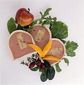 Three slices of liver pate with apple, garnished with salad