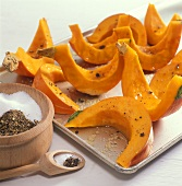 Seasoning pumpkin slices on baking sheet with salt & pepper