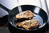 Frying pork chops with sage in cast-iron frying pan