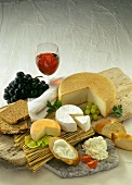 Various types of cheese with bread, grapes and red wine