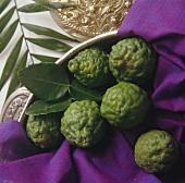 Kafir limes on purple cloth in a bowl