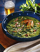 Pea soup with bacon and sausages in blue soup bowl